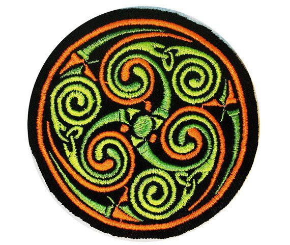 This is an embroidered patch featuring the ancient symbol of Celtic Spirals, which represent the paths of evergy through life, each piece is a different aspect or person, and each spiral is where we intertwine into beauty.  The size is 3.9 or 10cm across.  This symbol was designed by Jessie Matheny at Psysub using Adobe Photoshop, using a multi-layered system. It was then programmed into an embroidery pattern.  We used neon poly string to embroider this symbol onto a sturdy, thick, knit…