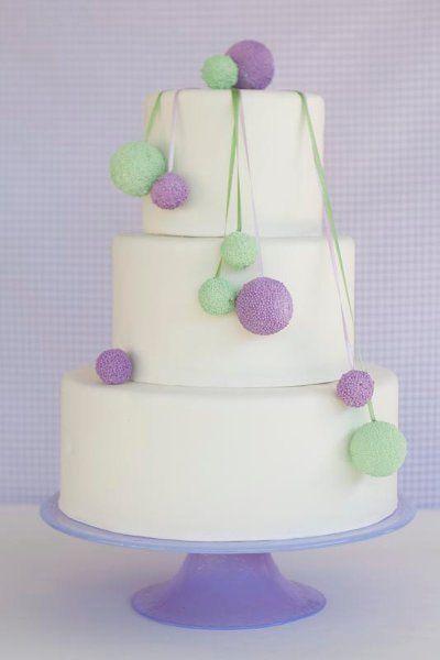 Una tarta muy original, adornada con pompones verde y lavanda / Modern white wedding cake with violet and green pom poms