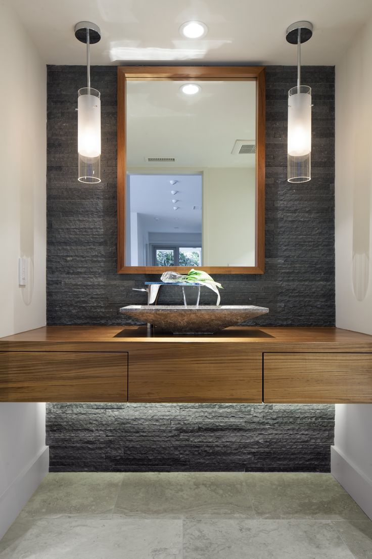 A modern bathroom with natural stone accent wall and pendant lights, under bench lighting.