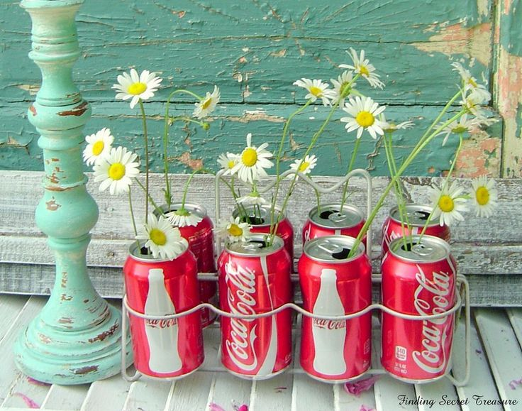 Soda cans as vases.  The daisies make such a sweet statement with the Coca Cola cans.  Might be fun for a young girl's birthday party...use her favorite soda cans, add the flowers...A great BBQ Party centerpiece too.