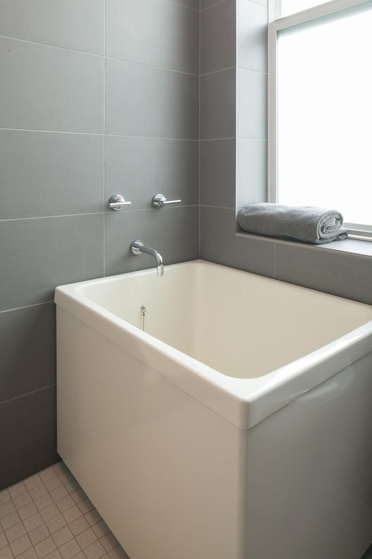 Japanese soaking tub - ofuro tub. Square with a built-in seat. Takes up minimal amount of space. This one is freestanding.