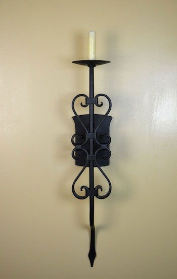 As Spanish interior lighting, the Barcelona Sconce is a traditional Spanish style wall sconce. These Spanish lighting fixtures feature a single imitation candle with dripping wax. Finished in a weathered black iron, The Barcelona Sconce features classic, hand forged Spanish scrollwork, held up by a unique backplate. Fit for any simple Spanish style home, this Spanish wall sconce is subtle, yet inviting enough for any interior space.