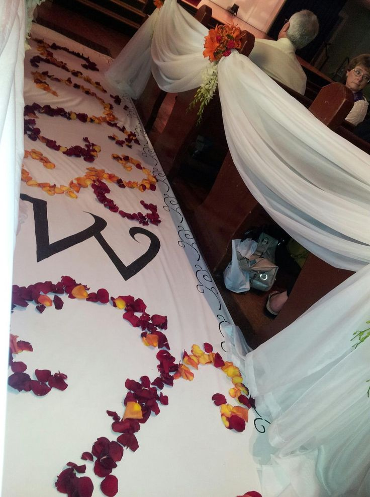 Custom hand painted aisle runner with monogram decorated in rose petals.