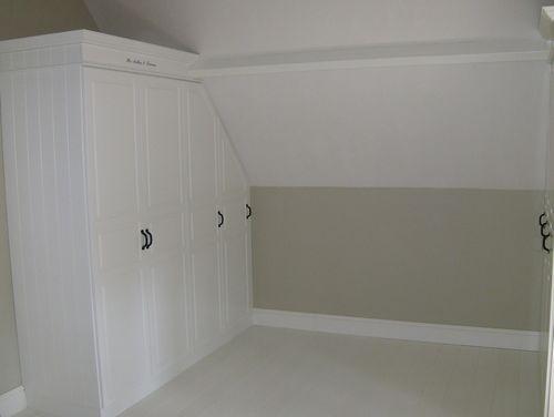 Inbouwkast met paneeldeuren en letterstickers onder schuin dak
