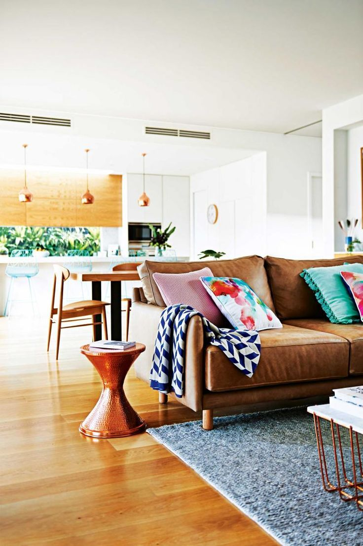 Tan sofa, white walls, light wooden flooring, colourful accessories, copper furniture