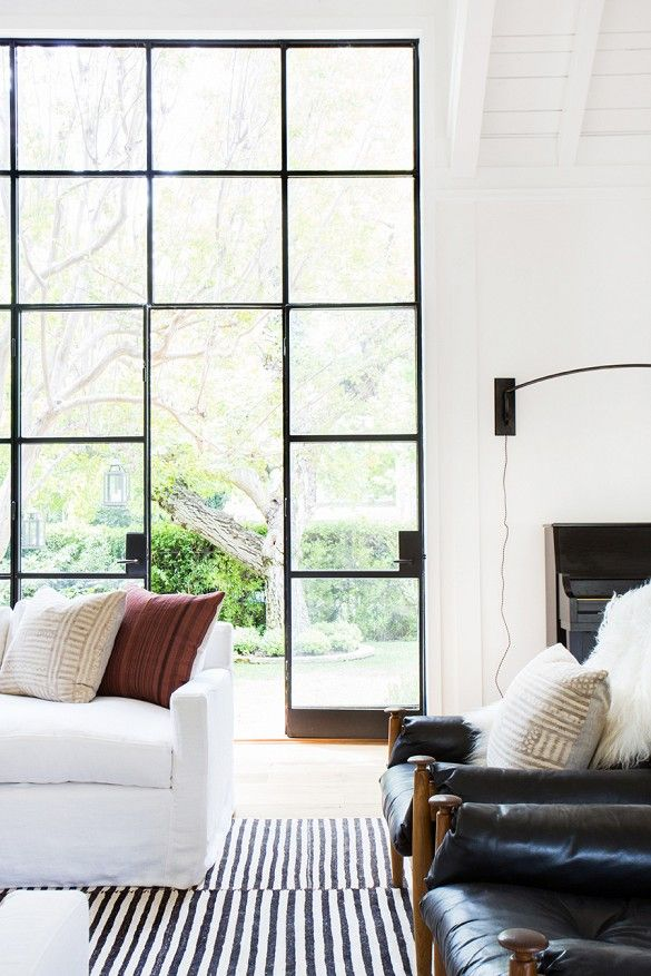 A bright and white space with patterned pillows and large windowed doors