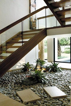 Artfully placed plants on a sectioned pebbled floor underneath the stairs create a Zen atmosphere, while glass windows allow natural light to filter in and a glimpse of the garden and outdoor pool.