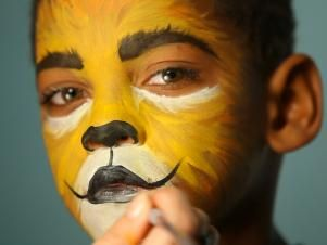 To give your child a ferocious lion's face for Halloween, simply paint a basic orange and yellow face. Then paint their top lip black and extend curving line up cheeks slightly. Paint their bottom lip black, then add black dots to white area above top lip. Add whiskers by brushing white paint in small, short strokes around mouth and cheek area. Add a line of black paint under eyes, angling down the nose to create those striking big-cat eyes.