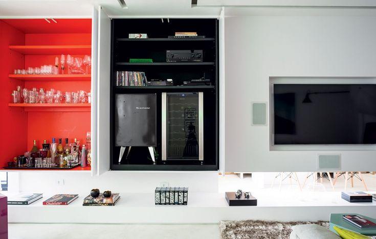 Na sala deste apê, onde vivia a blogueira Gabriela Pugliesi, a TV foi acomodada em uma estante sem pés, que esconde um pequeno bar e uma cristaleira. Projeto das arquitetas Stephanie Wolff e Beatriz Fujinaka, da Wolff + Fujinaka Arquitetos