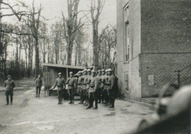 Appel van een groep militairen bij kasteel Oud-Poelgeest, waar tijdens de mobilisatie 1939-1940 een eenheid van het Korps Rijdende Artillerie was ingekwartierd. Achter de militairen zijn de buitenlatrines zichtbaar.