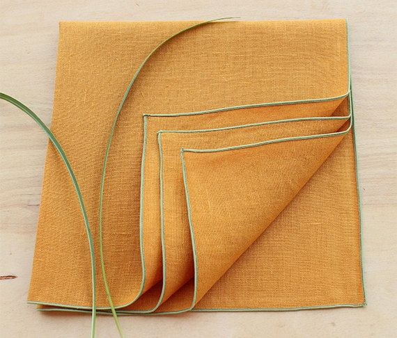 Set of four 100% linen dinner napkins in a gorgeous Autumn Gold color with orange undertones with contrasting rolled hem trim in sage green. Perfect