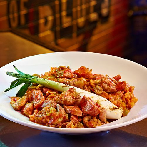 Jambalaya - Marinated chicken, white rice, andouille sausage, sweet peppers and roasted green onions in a spicy traditional jambalaya sauce