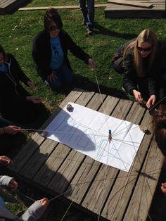 El rotulador está unido a 8 cuerdas, y el grupo, trabajando de manera conjunta tiene que escribir una palabra moviendo sólo la cuerda que tiene en su mano cada uno.