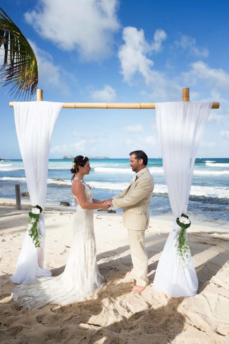 A simple and elegant beach wedding arch, bamboo and white draping #stbarth #goldnguestevents  Picture by Francois Vochelle Photography www.goldnguest.com