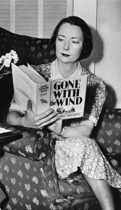 "Margaret Mitchell reading a copy of her novel ""Gone with the Wind""."