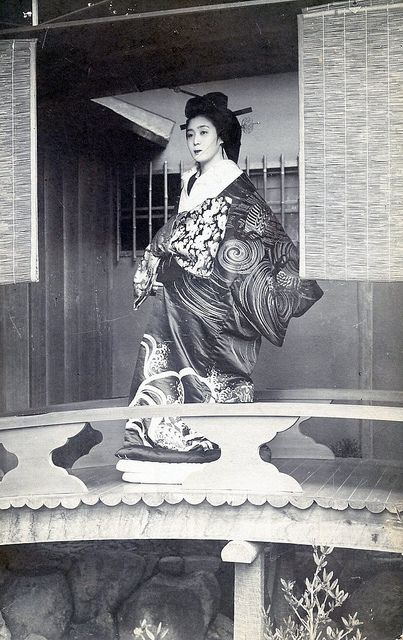 """Yoshiwara 1910 - Written in English on the back of this postcard is the following: """"This distinguished courtesan, has the air & carriage of a 'grande Dame', while her clothes are the costliest to be bought, such as only royalty is supposed to afford. She is standing on a bridge balcony to her house which is furnished as elegantly as that of a Queen."""""""