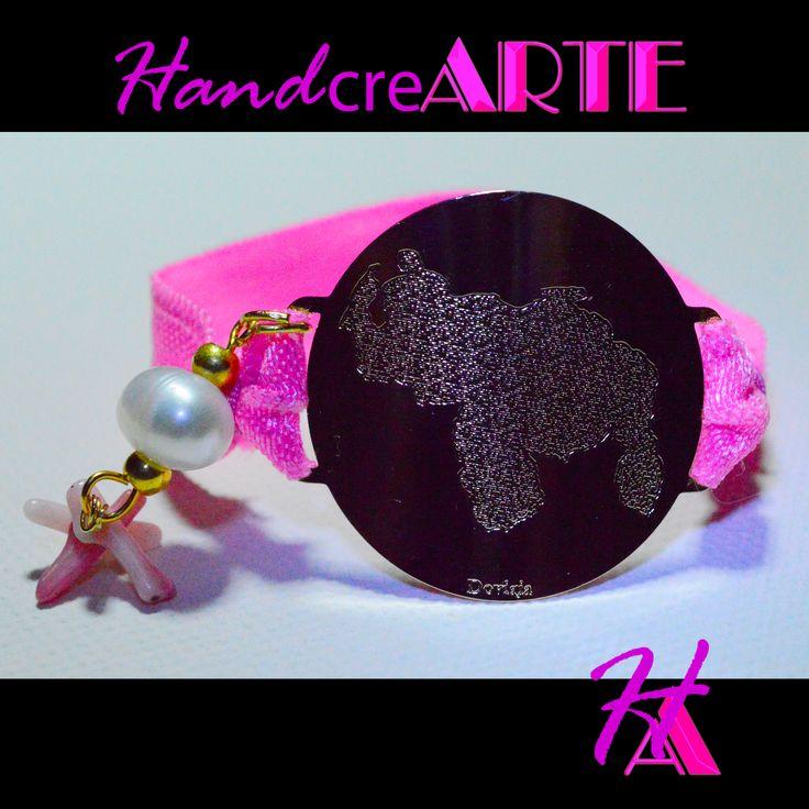 pulsera elastica rosa, con dije en oro laminado Mapa de venezuela, perla cultivada y coral rosa.