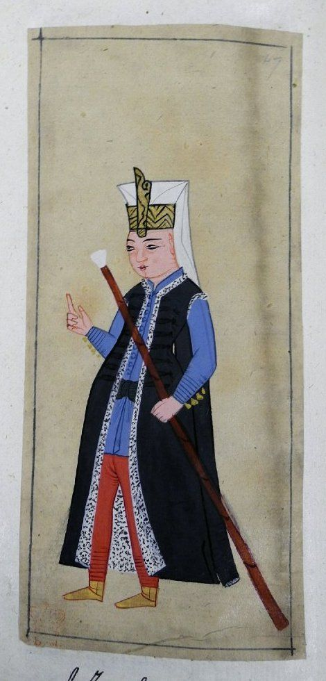 Yeniçeri. Very young Janissary wearing the head-dress with a plume-holder and carrying a staff (asa). Black sleeveless kaftan with fur lining. Blue tunic, dark blue kuşak, red tights and yellow ankle boots.