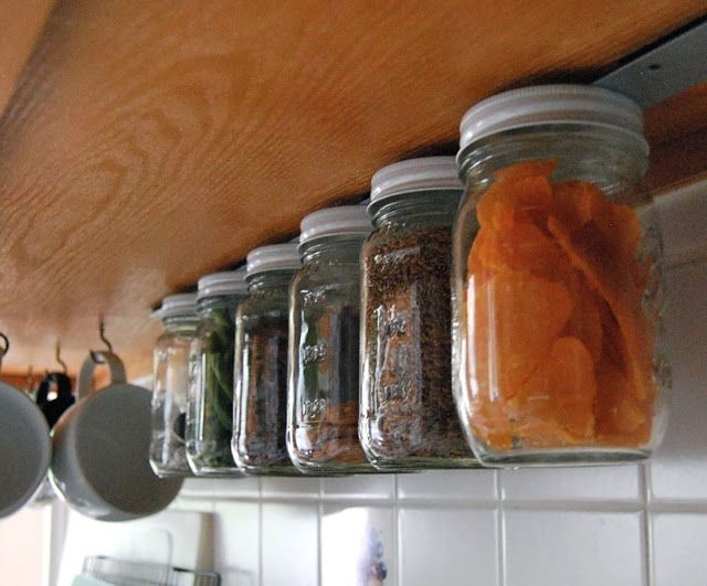 """Someone took a magnetic strip and mounted it under their kitchen cabinet.  Then they took metal top jars and hung them, magnetically, from u..."""
