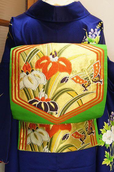 美しい黄緑色の地に牡丹や杜若の花々に遊ぶ蝶々が大胆な六角形にかたどられた華やかな袋帯です。