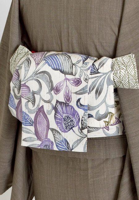 詳細                    サイズ     全長約400cm 幅約17㎝                色     オフホワイトに紫・青/深緑                        素材     絹100% (一部指定外繊維ぜんまい綿使用)                 生産     日本           仕立て     半幅帯           着用時期     盛夏を除く3シーズン           TPO     カジュアル        ■江戸紅型の職人による手染めです。 小幅(約36cm)の型で染めた反物を裁断して使用しているため、商品ごとに柄の出る部分が異なります。 また、柄・色の配置は商品写真と異なる場合がございます。※柄のご指定はお受けできかねます。  ■紬生地を使用しているため、糸の節が色ムラとなって見られることがございます。 素材の持つ特性・味わいとしてご理解の上お求め下さい。   ■店舗にてこちらの商品をお問い合わせいただく場合には、商品名と商品番号をお知らせください。