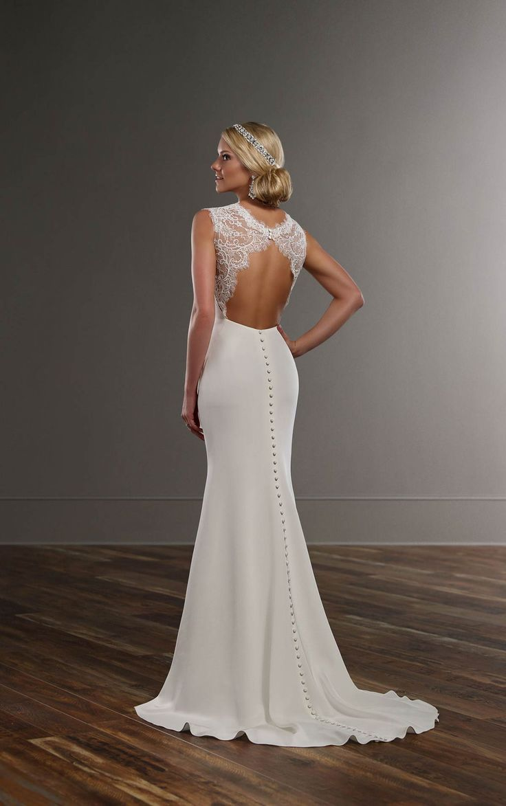Simple. Sleek. Sexy. This Martina Liana designer wedding gown is made from silk Moroccan and lace. The bodice boasts a low V, soft draping and lace sleeves and keyhole back. The skirt wraps around into a court train embellished with fabric-covered buttons.
