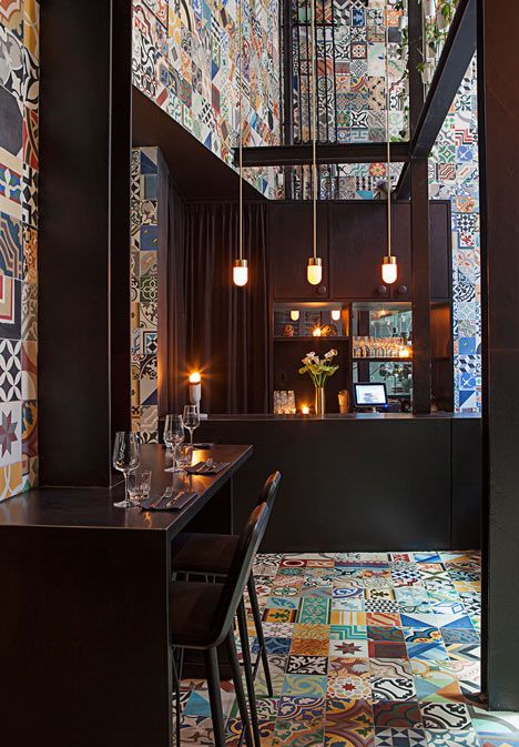 Brightly-coloured patterned ceramic tiles line the walls, floor and stairs of this South American restaurant in Copenhagen, designed by Danish studios BIG and Kilo Design