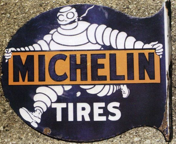 Flanged sign advertising Michelin Tires displaying the Michelin Man smoking a cigar which was later removed.