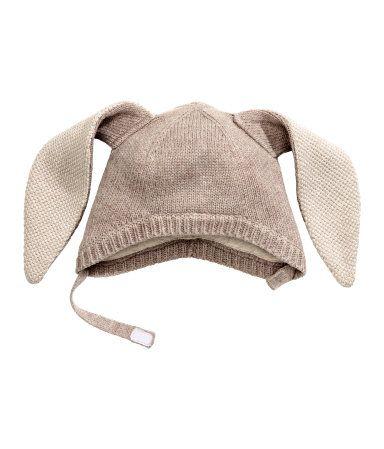 Taupe clair. Bonnet en maille de coton mélangé. Modèle surmonté de longues oreilles cousues. Lanière avec fermeture auto-agrippante sous le menton. Doublure