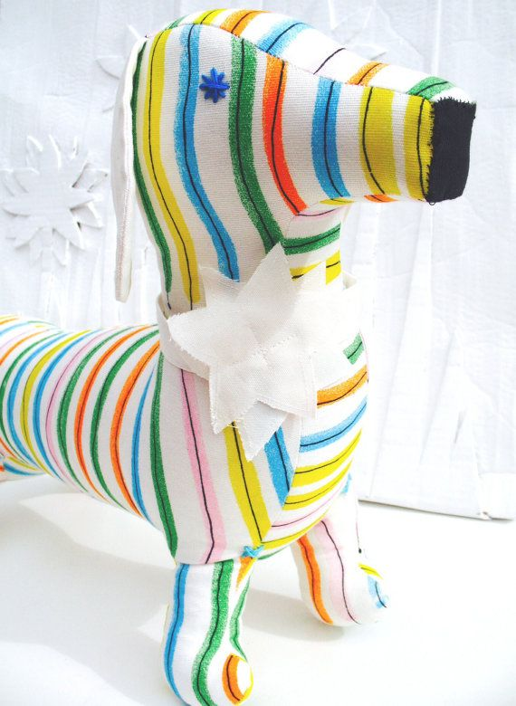 A cute, modern retro fabric daschund. This stylish toy sausage dog is handmade from contemporary, striped Scandinavian fabric, filled to capacity with