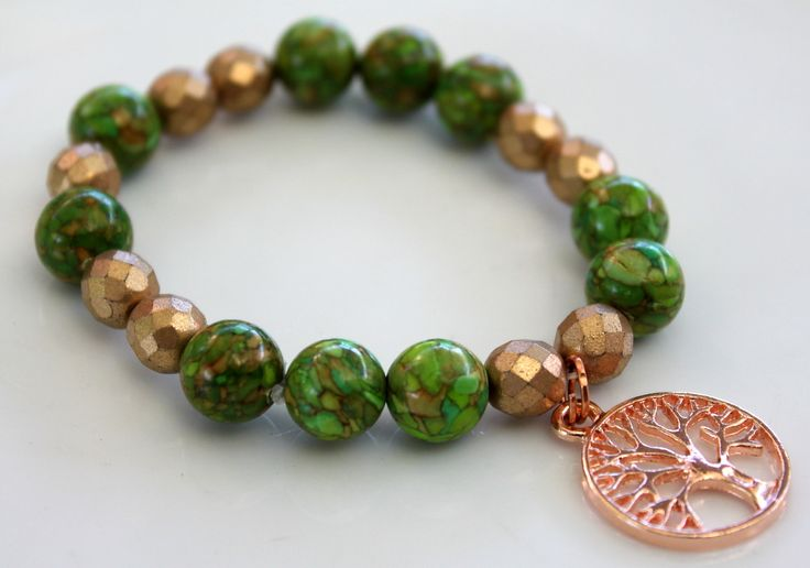 """Contemporary Bracelet B089  $25 This bracelet is made up of Green Turquoise (stabilised) Gemstone Beads and Czech Fire Polished Glass Beads in light Gold. I added a Rose Gold Plated """"Tree of Life"""" Charm in the centre.  Easy to get on and off, this is a great piece to wear alone or stacked with other bracelets in your wardrobe. Made with two layers of sturdy elastic cord, the bracelet will comfortably fit an average size wrist.  Length – 18cm."""