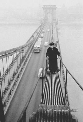 """Budapest, 1962, január 18. Éjjel-nappal vigyáz a Lánchídra a hídmester. Azt is kevesen tudják, hogy a hidakra éjjel-nappal jól képzett szakemberek vigyáznak és a legkisebb műszaki, vagy egyéb hibát azonnal kijavítják. A Lánchíd """"őre"""" a 60 éves Paréj János hídmester, aki a korát meghazudtoló fürgeséggel mozog a vasszerkezetek között, - még éjszaka is - végigjárja a mély lánckamrákat, felmegy a pillértetőkre és ellenőrzi a hajók jelzőlámpáit. Emellett fülkéjéből állandóan figyeli a hidakat."""