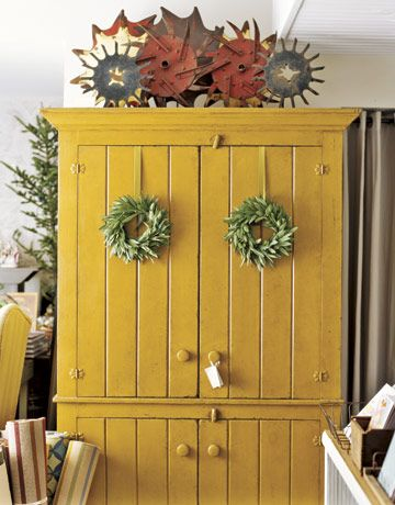"Fragments of old farm equipment are displayed atop a High Falls Mercantile Collection Mustard 4-Door Armoire. ""Many of the new things here in our store are based on traditional forms,"" says Jeff.   - CountryLiving.com"