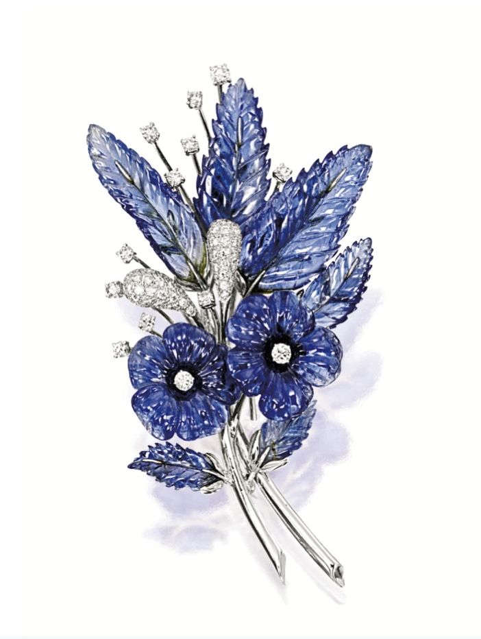 "CARVED SAPPHIRE AND DIAMOND ""FLOWER"" BROOCH    Of floral motif design, set with carved sapphire flowers and leaves together weighing approximately 50.00 carats, decorated by brilliant-cut diamonds together weighing approximately 1.00 carat, mounted in 18 karat white gold."