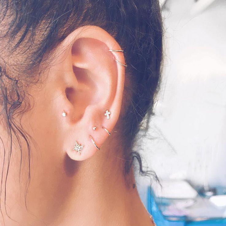 Piercings distribuidos en toda la oreja.