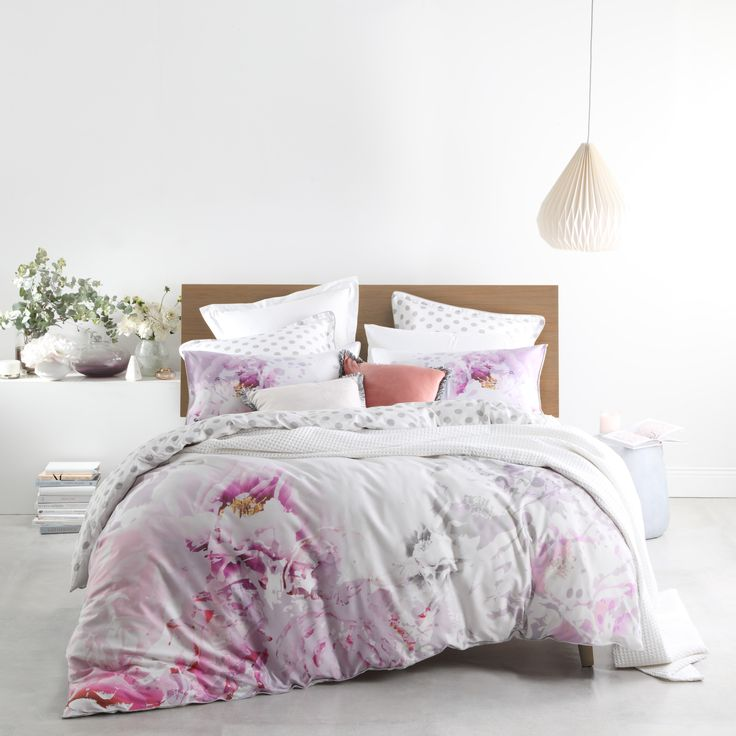 Peony Blush is a contemporary floral. The large scale and painterly watercolour technique in hushed tones of pink and purple is artistically stunning, while the liberal use of white exudes freshness and light. Silver polka dots on the reverse give a whimsical turn-back contrast, elegantly finished with silver piped edges. #loganandmason
