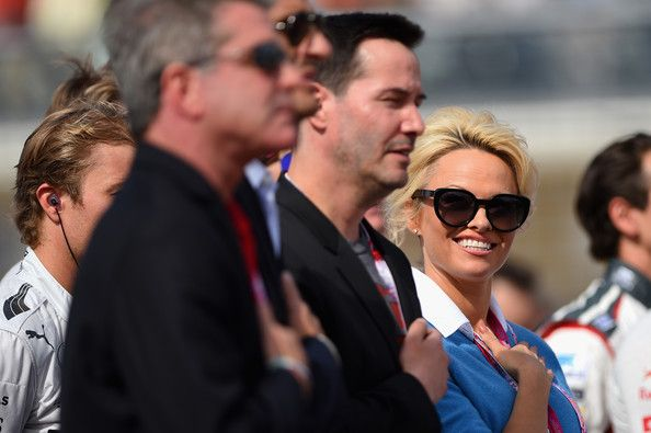 Keanu Reeves Photos Photos - Actors Keanu Reeves and Pamela Anderson stand for the national anthem before the United States Formula One Grand Prix at Circuit of The Americas on November 2, 2014 in Austin, United States. - F1 Grand Prix of USA