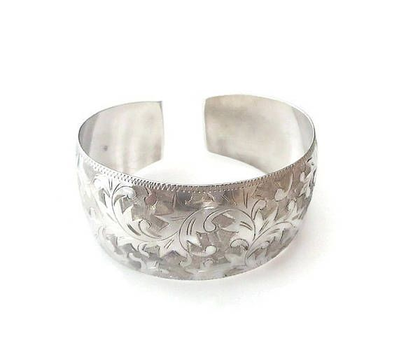 Vintage Japan Sterling wide damascene style cuff bracelet. Age: estimated circa 1950s - 60s, mid century. Measurements: It is approximately 7-1/2 long (interior circumference) x 1-1/4 wide (at the widest point). Weight: it weighs approximately 28 grams total. Condition: it is in overall good condition, consistent with age. There are some surface scratches mostly on the interior area. There is one black dot on the metal as seen in photo #4, but otherwise no tarnish. A well made brace...