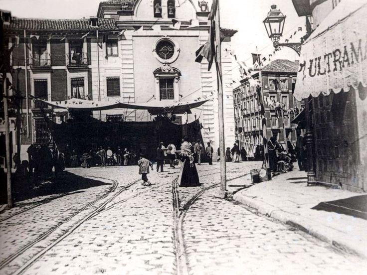 Plaza de la Cebada (1890), al fondo la Iglesia de Nuestra Señora de Gracia o de la Vera Cruz (esquina calle Humilladero), derribada en 1903, quedando un solar utilizado al comienzo de los años cincuenta para la ampliación del Mercado - el proyecto conllevo el derribo del antiguo edificio de hierro, siendo sustituido por el actual de hormigón -.   Puestos del mercado delante de la Iglesia. Plaza de la Cebada, a partir del siglo XV, un espacio vacío en los extramuros de la Puerta de los Moros…
