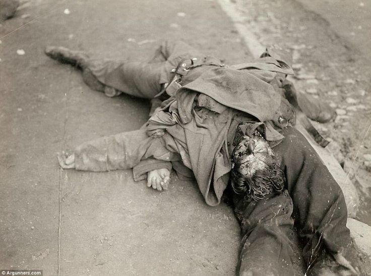 Bodies of German soldiers lying on top of each other in a French street gutter. Photographed by Brigadier General Charles Day Palmer