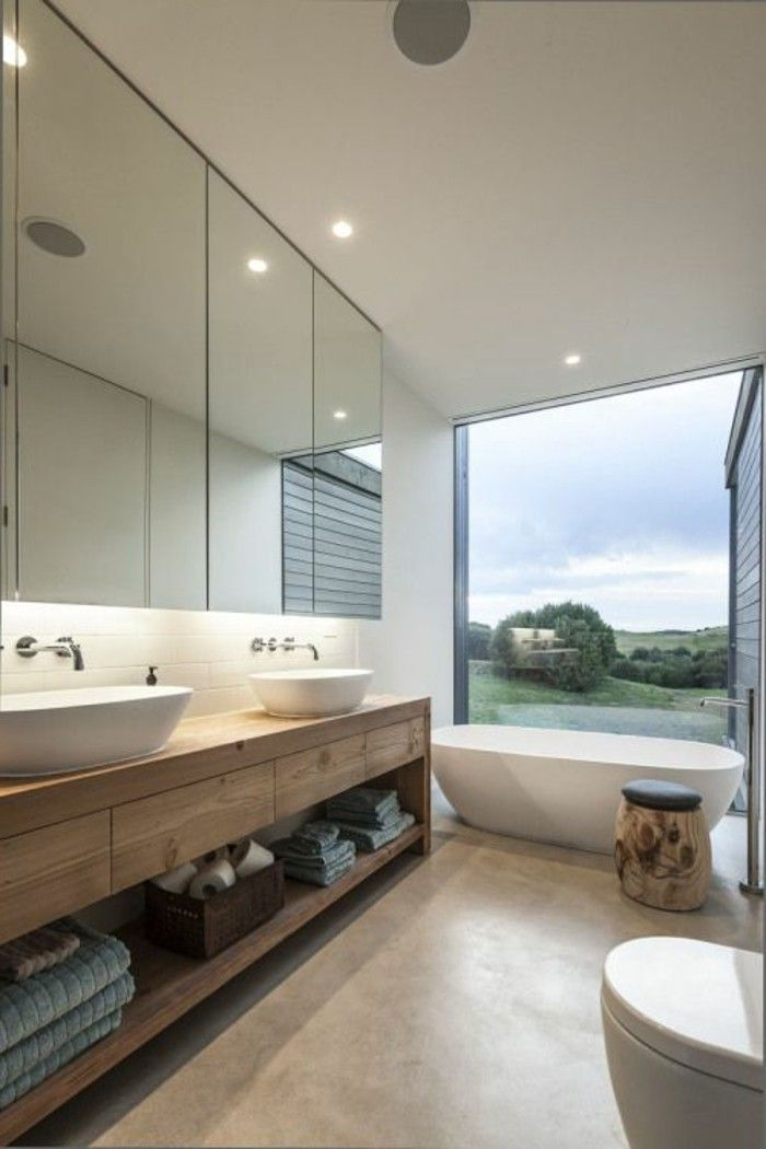 salle de bain avec grande fenêtre avec vue lavabo blanc meuble miroir, sol beige, meubles en bois clair