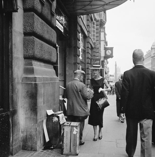 Audrey Hepburn buys a newspaper from a street vendor in London, 1953.