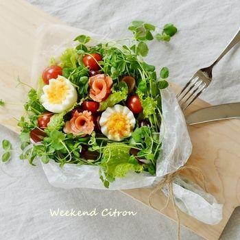 テーブルに花が咲いたように華やぐブーケサラダ。ゆで卵やスモークサーモンで花を作って飾りましょう。ブドウやプチトマトをポンポンと置いたら、愛らしさ満点。深めのタッパーに入れれば、持ち運びも簡単です。