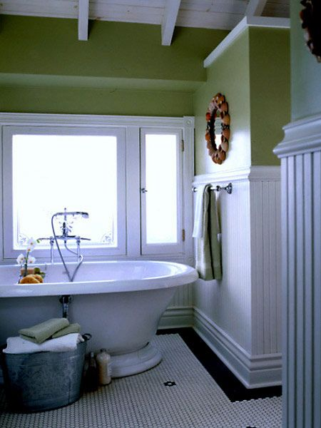 In this master bath, a serene combination of white paneling and tile flooring, sea-green walls, and a huge tub offers a sanctuary. (Photo: Photo: Alec Hemer; Stylist: Michelle A. Zuniga)