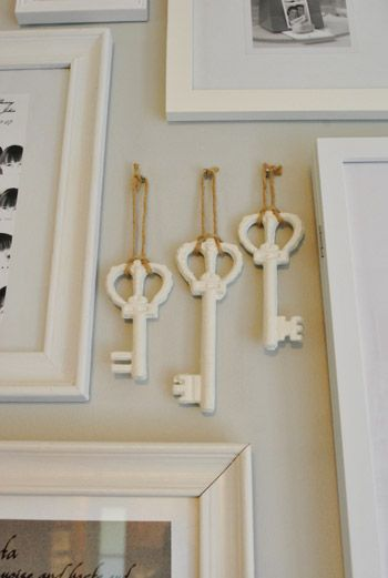 Antique keys painted white and hung in the midst of a white frame picture mural.