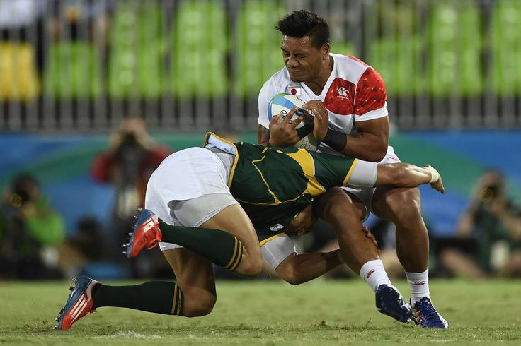 Japan's Lomano Lemeki is tackled by South Africa's Juan de Jongh in the mens rugby sevens bronze medal match between Japan and South Africa during the Rio 2016 Olympic Games at Deodoro Stadium in Rio de Janeiro on August 11, 2016. / AFP / John MACDOUGALL