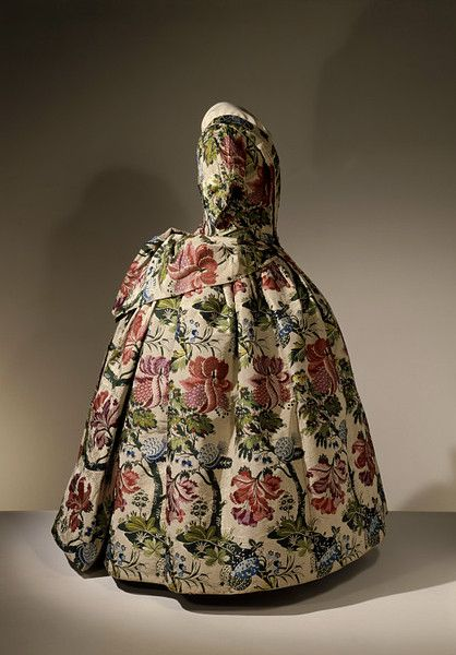 Mantua, England,1740 (made)  Brocaded silk, hand-sewn with spun silk and spun threads, lined with linen, brown paper lining for cuffs, brass, canvas & pleated silk. One of the mantua's characteristics was a long train, sewn as a flat piece of silk & arranged with each wearing. The train was folded up, then folded in & draped over a loop of thread on either side of the waist. Pinning up & draping a train successfully was an art & required the help of maids to achieve the perfect effect.