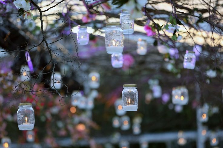 Glass jar with tea light hanged to the ceiling made of branches