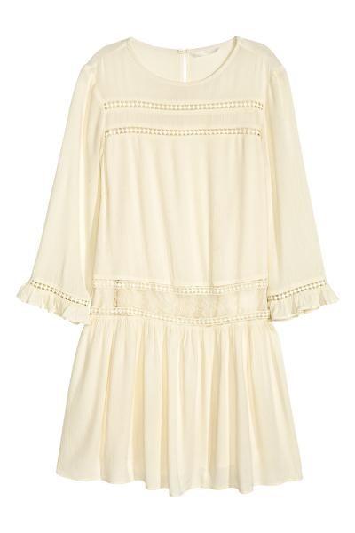 Crinklejurk: Een korte jurk van crinkleviscose met ingezette kanten stroken vooraan en op de heupen. De jurk heeft driekwart mouwen met een kanten biesje en een volant onderaan en een splitje met een knoop in de nek. Gevoerd.