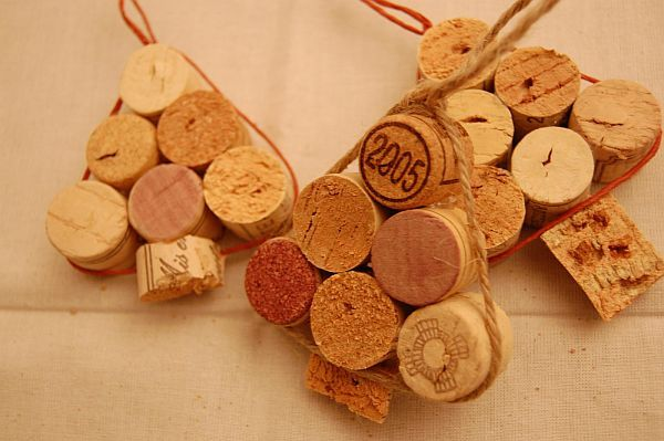 You could paint the corks green, silver, gold, red and let them dry. Then glue them together in a tree shape, tie ribbon or something else around them leaving enough at the top to hang on your christmas tree.  Easy enough for the kids.